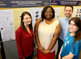 SLP students stand with research poster on using NIRS to measure hemoglobin concentration during stretched-vowel speech