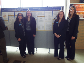Students pose with research poster on the effects of cognitive behavioral and exercise therapies on chronic pain