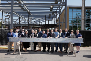 Trustees, friends and members of the leadership team pose in front of the final beam to be erected in the Henry Science Center.
